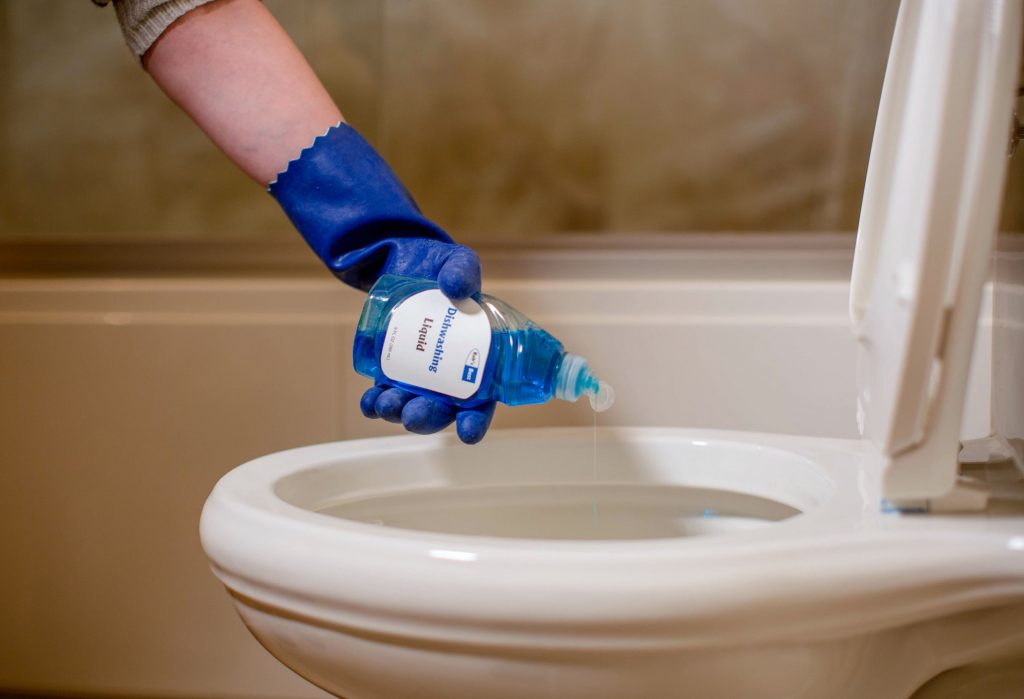 detergente sendo colocado no vaso sanitário