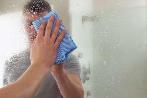 homem limpando espelho com pano azul