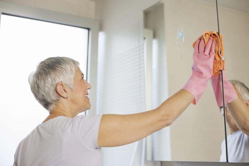 mulher limpando espelho