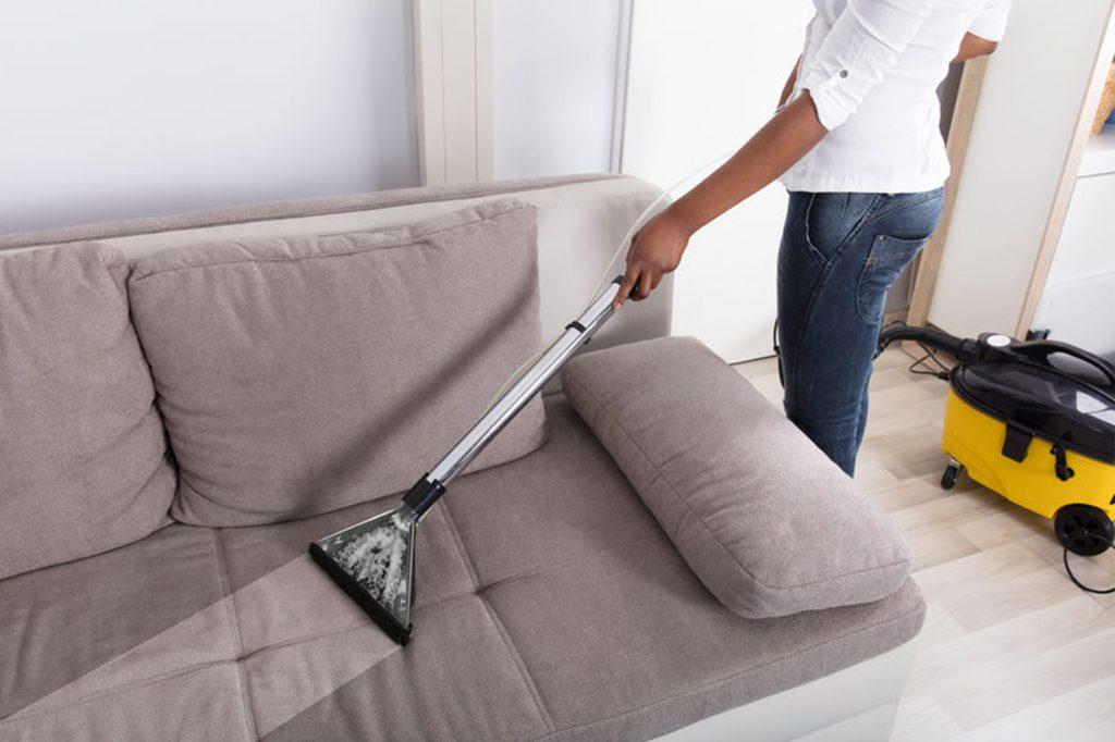 pessoa limpando sofá