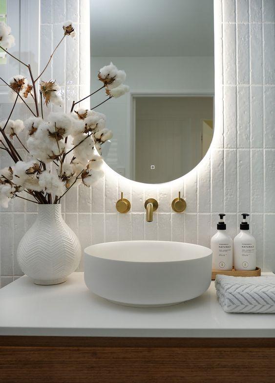 espelho com led e flores em bancada de banheiro