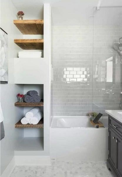 banheiro em tons brancos com prateleiras